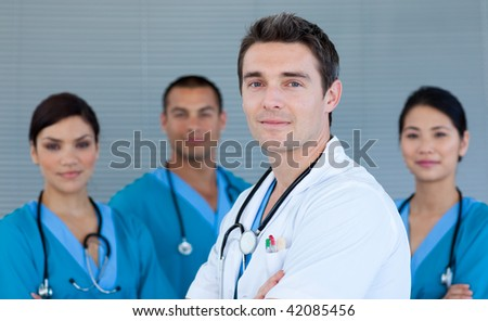 Young male Doctor with his team in the background looking at the camera - stock photo