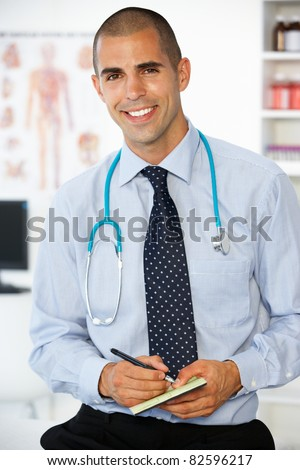 Young male doctor writing prescription - stock photo