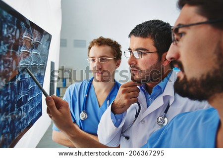 Young male doctors looking attentively at x-ray and discussing it - stock photo