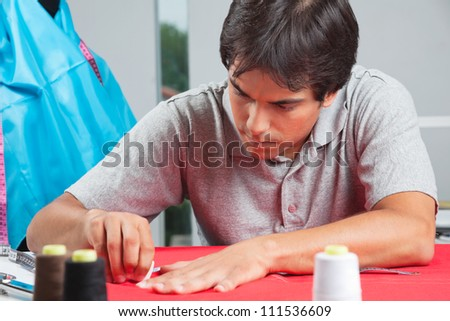 Young male dressmaker drawing line on a red fabric with chalk