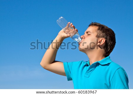 young male drinking water against blue sky - stock photo