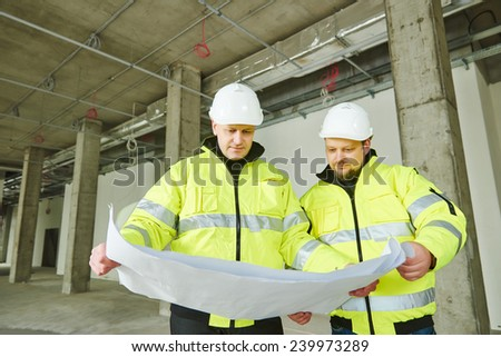 young male engeneers workers foreman at a indoors building site with blueprints - stock photo