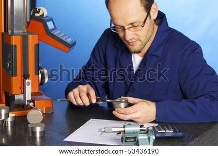 Young male engineer in blue overall measuring a metal part with caliper, isolated on blue background. - stock photo