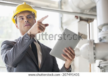 Young male engineer with digital tablet pointing away in industry - stock photo
