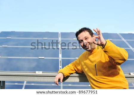 Young male engineer with solar panels in background - stock photo
