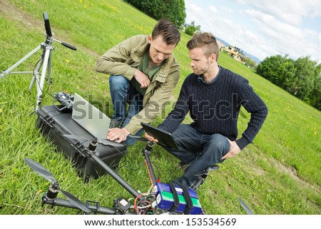 Young male engineers discussing over digital tablet and laptop by UAV drone in park - stock photo