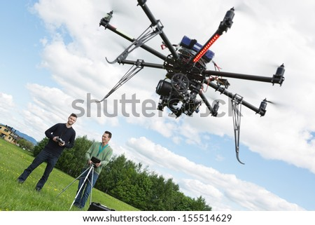 Young male engineers operating UAV helicopter against cloudy sky - stock photo