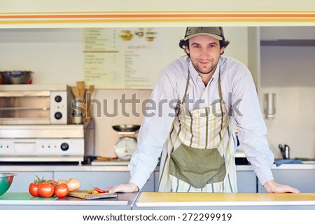 Young male entrepeneur standing confidently in his food stall where he makes and sells takeaway food  - stock photo