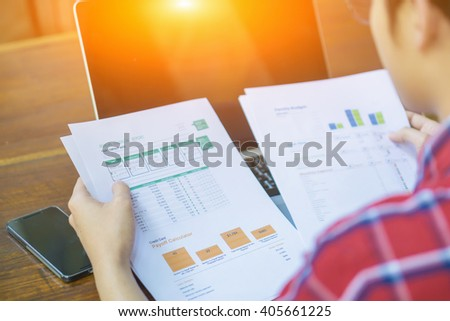 Young male entrepreneur working sitting at a desk typing on his laptop computer in a home office, view from above,young entrepreneur analyzing notebook,freelancer work ,selective focus,vintage color - stock photo