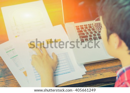 Young male entrepreneur working sitting at a desk typing on his laptop computer in a home office, view from above,young entrepreneur analyzing notebook,freelancer work ,selective focus,vintage color
