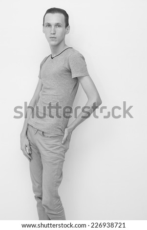 Young male fashion model against studio wall in black and white - stock photo