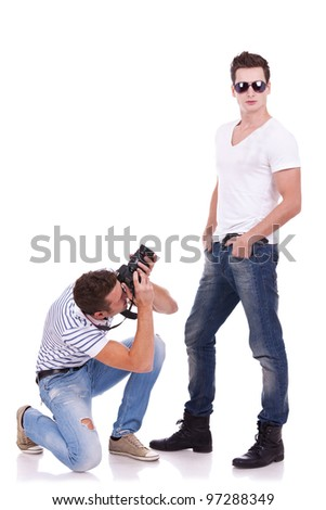 young male fashion model posing for a professional photographer on white background. young man wearing sunglasses being photographed by a young artist - stock photo