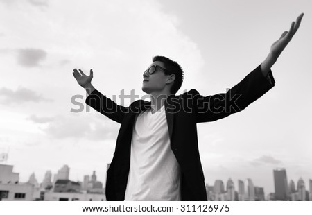 Young male feeling happy and confident with a city background.  - stock photo