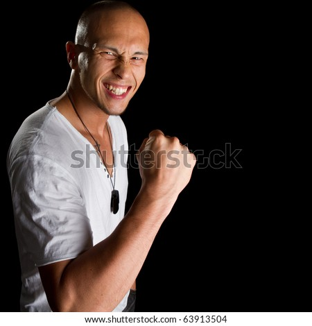 Young male filipino model over a black background is gesturing with his hand.