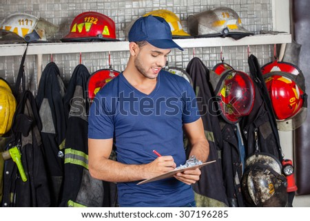 Young male firefighter writing on clipboard at fire station - stock photo