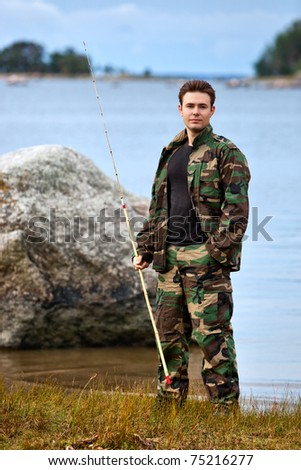 Young male fisher on lake shore. - stock photo
