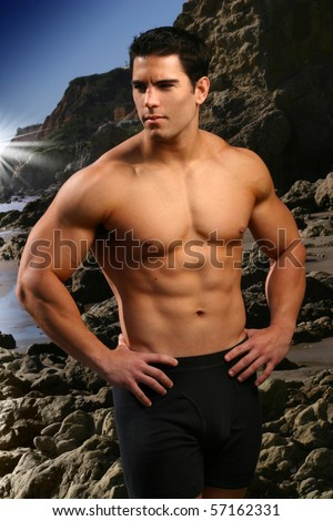 Young male fitness model at the beach with rocks and blue sky - stock photo