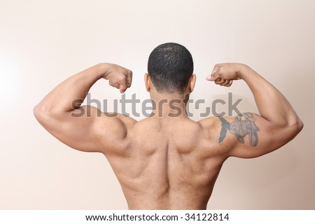 Young male flexing back and arm muscles - stock photo