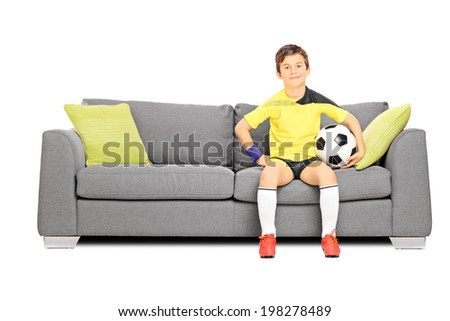 Young male football fan sitting on couch and holding a ball isolated on white background - stock photo