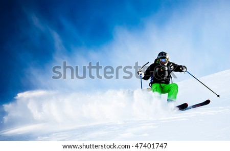 Young male freeride skier over blue sky turning in powder snow; black jacket; green pant; horizontal orientation - stock photo