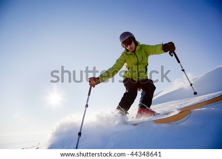 Young male freerider skier moving down in snow powder at sunset; italian alps.