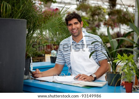 Young male garden center employee at check out counter - stock photo