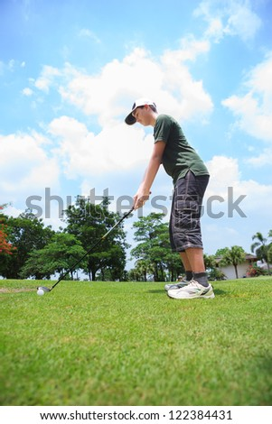 Young male golf player at the course ready to hit the ball - stock photo