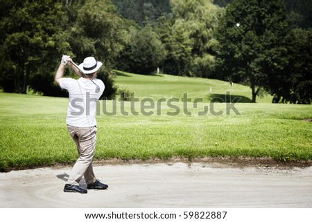 Young male golf player chipping in bunker with forest in the background. - stock photo