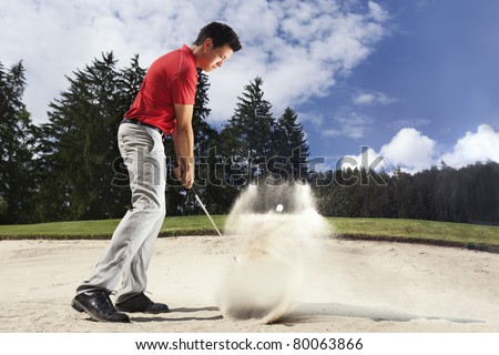 Young male golf player in red shirt and grey pants chipping golf ball out of a sand trap with sand wedge and sand caught in motion. - stock photo