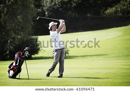 Young male golf player pitching at golf course with golf bag standing aside. - stock photo