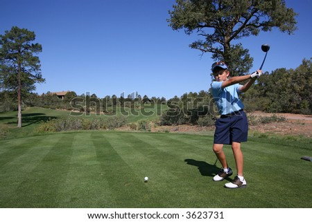 Young male golfer about to hit a ball on a beautiful golf course with blue sky - stock photo