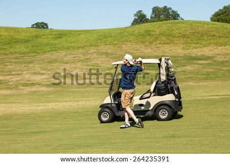 Young male golfer hits a line drive down fairway on golf course - stock photo