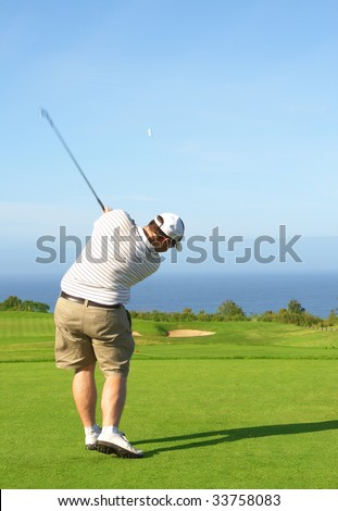 Young male golfer hitting the ball from the fairway next to the ocean on a beautiful summer day