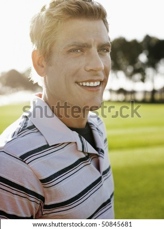 Young male golfer on court, smiling - stock photo