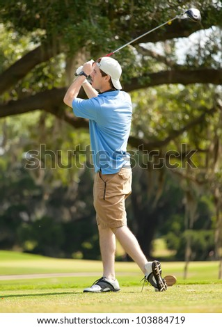 Young male golfer playing golf - stock photo