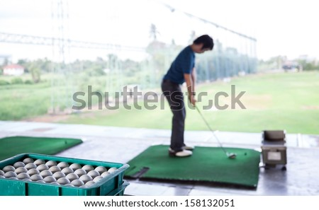 Young male golfer practicing his drive (Selective Focus at Golf ball tray) - stock photo