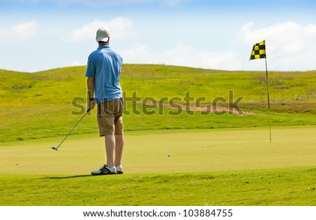 Young male golfer putting for a drop in the pin - stock photo