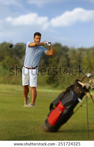 Young male golfer swinging golf club, following golf ball. - stock photo