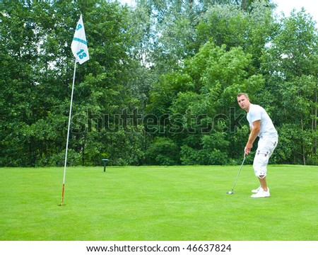 Young male golfer with club on golf course.