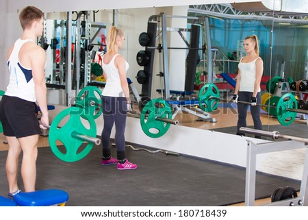 young male gym instructor helping an young woman with weight training equipment on sport gym
