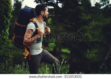 Young male hiker enjoying the scenery nature landscape while standing on mountain hill with green copy space area forest for your text message or advertising content, traveler with a backpack resting - stock photo