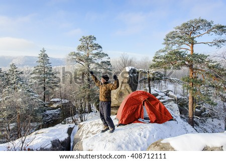 Young male hiker is standing with his arms raised next to his red tent on a beautiful mountain summit. Winter base camp on a cold sunny morning. Winter hiking clothes. - stock photo