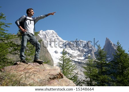 Young male hiker pointing to somewhere; mountain scenic, Mont Blanc, Italy. - stock photo