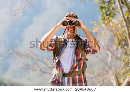 young male hiker using binoculars on top of the mountain - stock photo
