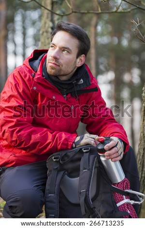 Young male hiker with backpack in forest - stock photo