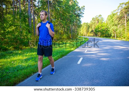 young male hiker with backpack walking alone on forest road - stock photo