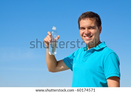 young male holding bottle of water against blue sky - stock photo