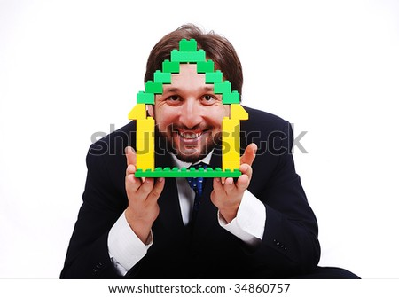 Young male holding homes made by cubes - stock photo