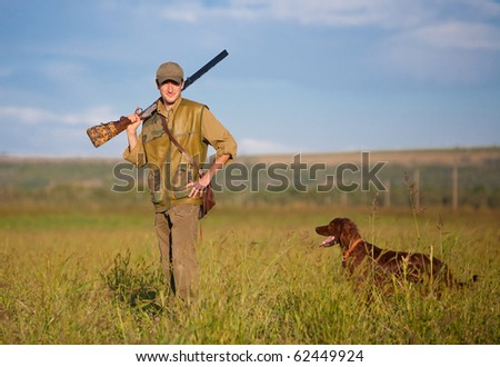 Young male hunter on the hunting field heading for the hunt. Dog waiting for the shot