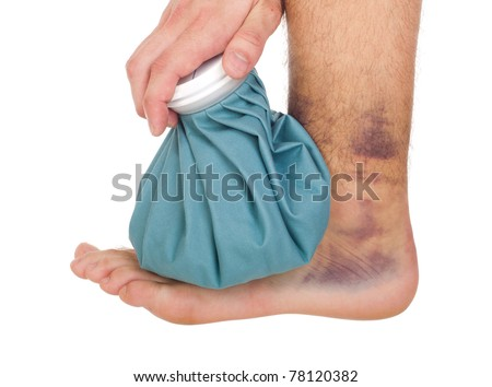 young male icing a sprained ankle with ice pack (isolated on white background) - stock photo